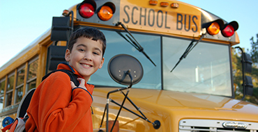A boy getting on a school bus